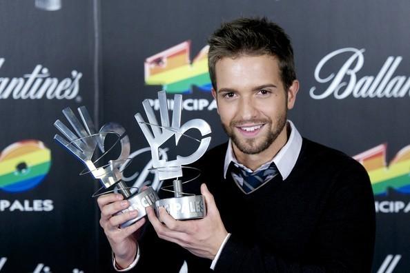 Pablo Alborán posando con los dos Premios 40 Principales