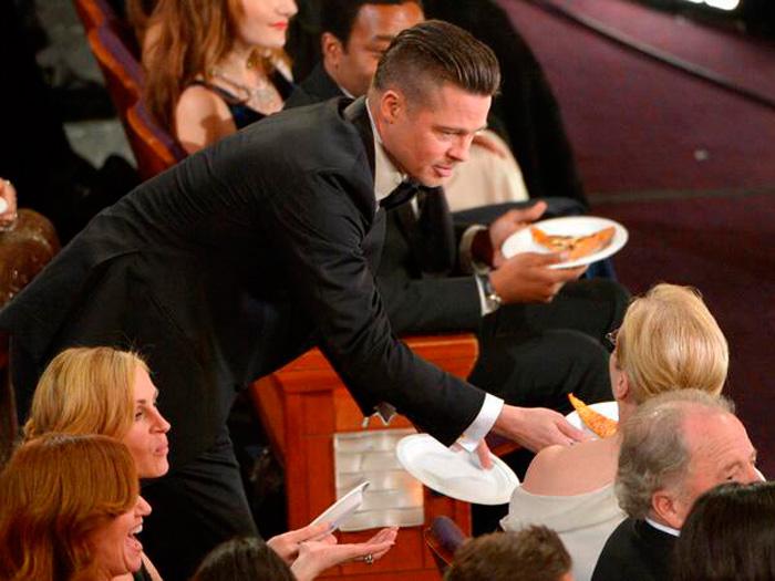 Brad Pitt repartiendo platos para comer la pizza en los Oscar-Fuente: twitter.whotalking.com