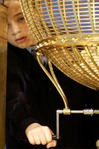 Una niña del colegio de San Ildefonso extrayendo una de las bolas