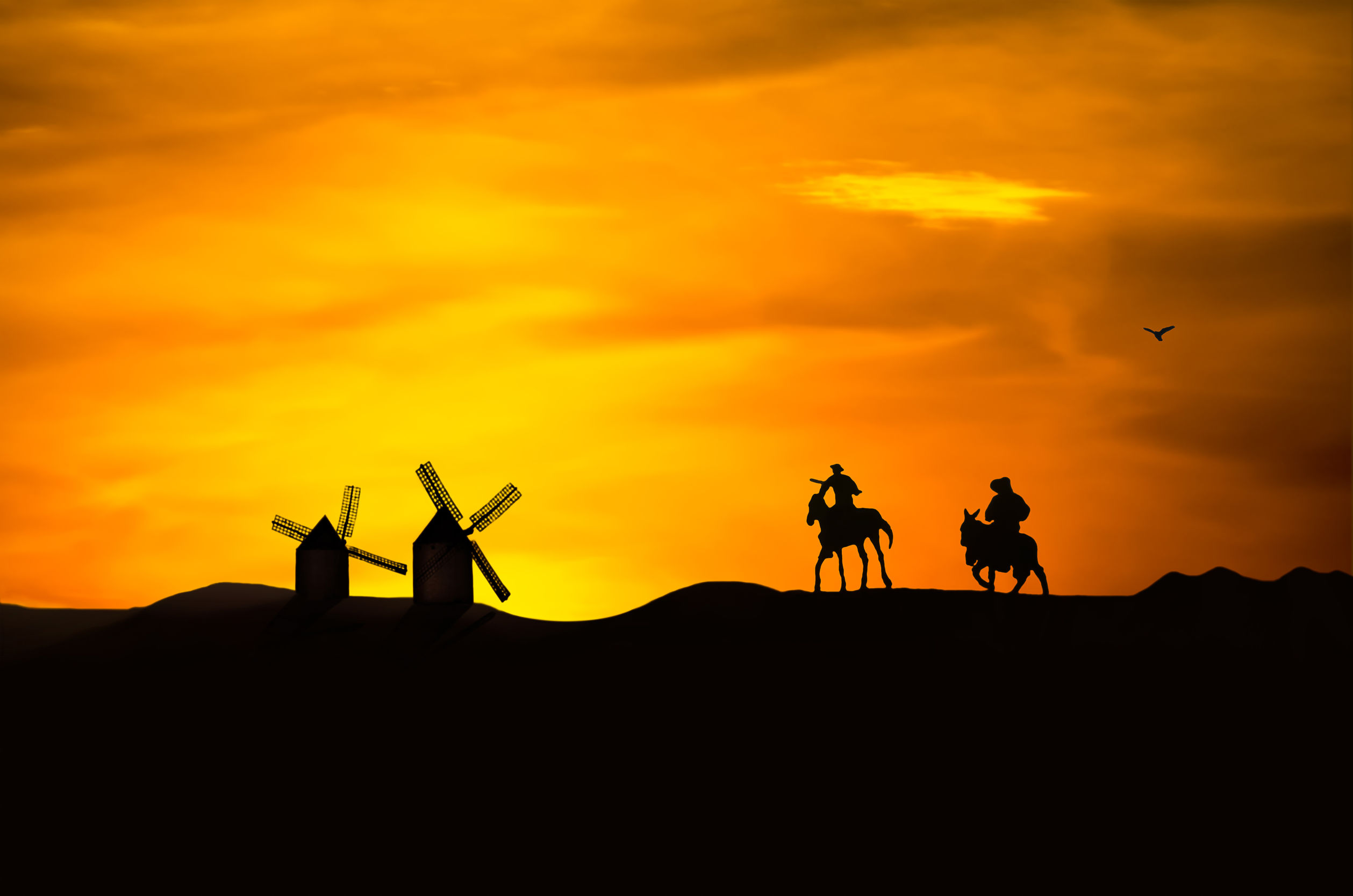 Don Quijote y Sancho Panza cabalgan hacia los molinos de viento.