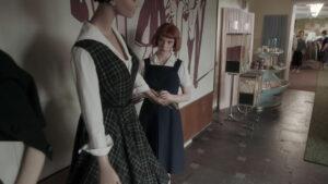 Beth Harmon mirando un vestido