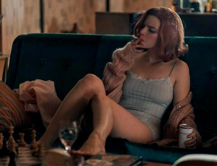 Beth Harmon fumando en el salón de su casa